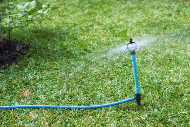 Sprinkle spray water to lawn field Premium Photo