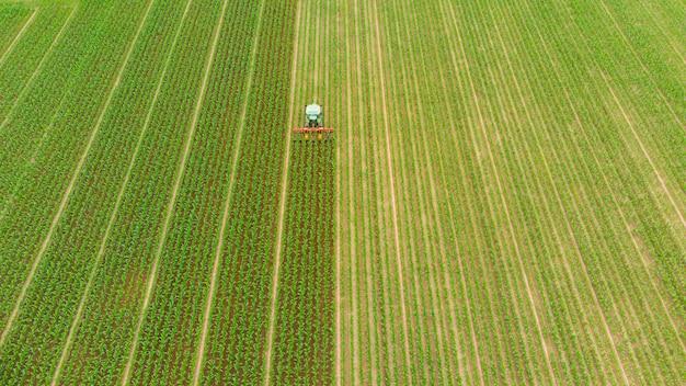空中:耕作地の農地、農業の職業、緑豊かな穀物のトップダウンビュー、イタリアのsprintimeに取り組んでいるトラクター Premium写真