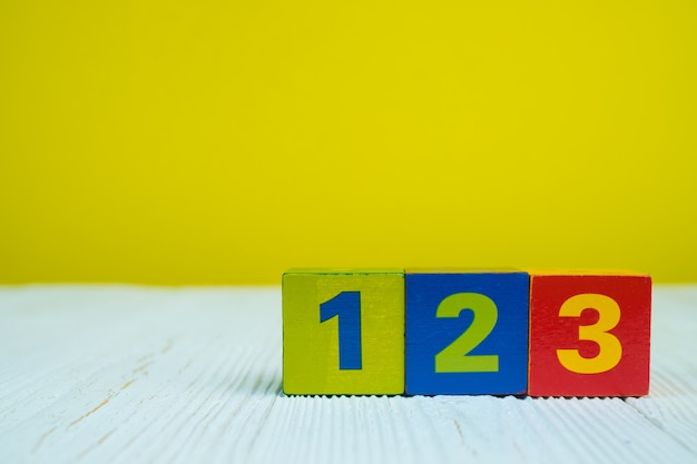 Square block puzzle number 1 2 and 3 on table with yellow Premium Photo