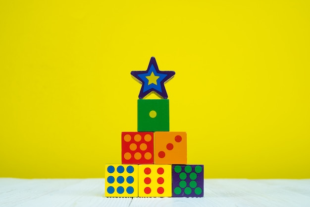 Square block puzzle toy on table with yellow background Premium Photo