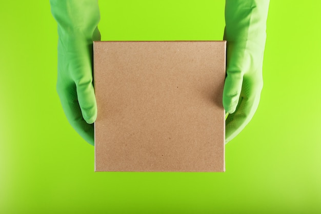 A square box in the hands with green rubber gloves on a green background. Premium Photo