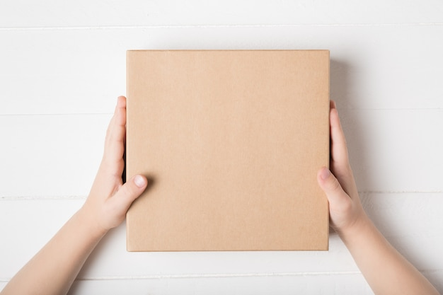 Square cardboard box in children hands. top view, white background Premium Photo