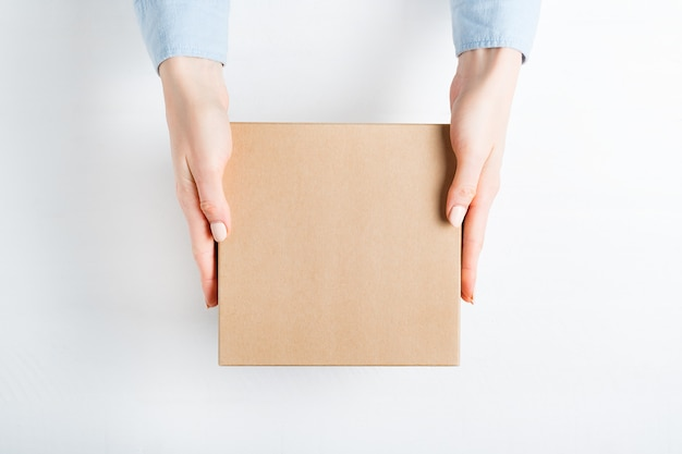 Square cardboard box in female hands. Premium Photo