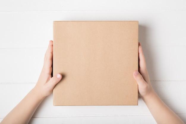 어린이 손에 사각형 골 판지 상자입니다. 상위 뷰, 흰색 배경 프리미엄 사진