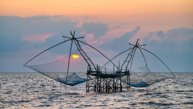 Square dip net with sunrise at pakpra, phatthalung, thailand Premium Photo
