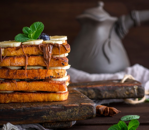 Square fried bread slices with chocolate and banana Premium Photo