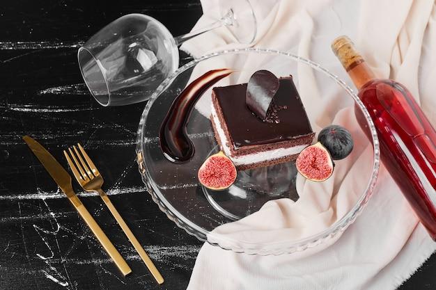 Una fetta quadrata di cheesecake al cioccolato su un supporto di vetro Foto Gratuite