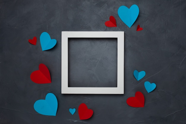Square white empty frame with hearts on gray textured background with copyspace Free Photo