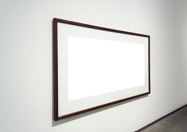 部屋の壁に暗いフレームが取り付けられた正方形の白い表面 無料写真
