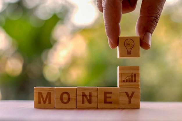 Квадратные деревянные блоки с денежными купюрами, идеями планирования покупок и изобретательностью покупок. Premium Фотографии