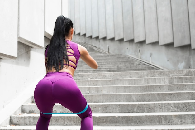 Squats. resistance band sporty young woman doing squat exercise Premium Photo