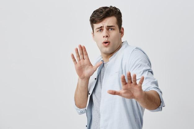 彼の女の子が彼を何かを非難しようとしている間彼の女の子が手のひらで一時停止の標識を示す黒髪のきしむ白人白人ハンサムな男。若い男が怖がって叫び顔をしかめ 無料写真