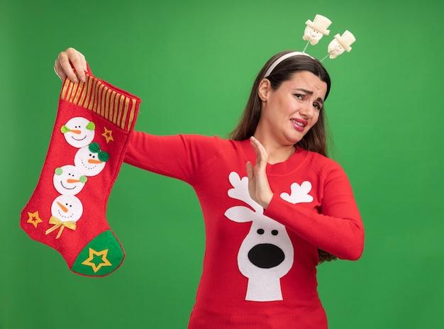 Брезгливая молодая красивая девушка в рождественском свитере с рождественским обручем для волос, держащая рождественские носки, показывая жест остановки, изолированный на зеленом фоне Бесплатные Фотографии