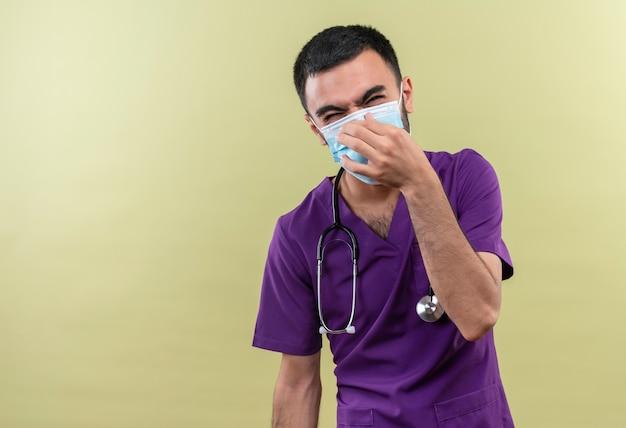 Schizzinoso giovane medico maschio indossa viola chirurgo abbigliamento e stetoscopio maschera medica naso chiuso su sfondo verde isolato Foto Gratuite