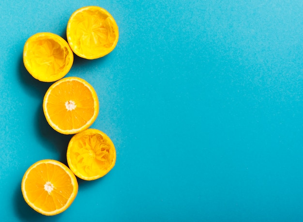Squeezed oranges on blue background Free Photo