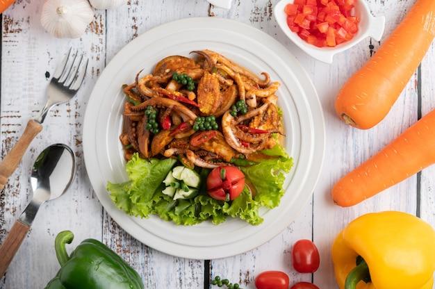 흰색 나무 바닥에 야채와 반찬과 함께 흰 접시에 카레 페이스트로 오징어 튀김. 무료 사진