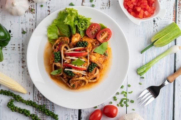 Кальмары обжаренные с пастой карри на белой тарелке с овощами и гарнирами на белом деревянном полу. Бесплатные Фотографии