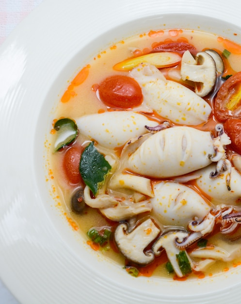 Squids and lemon grass spicy soup with mushrooms, tomatoes and herbs Premium Photo