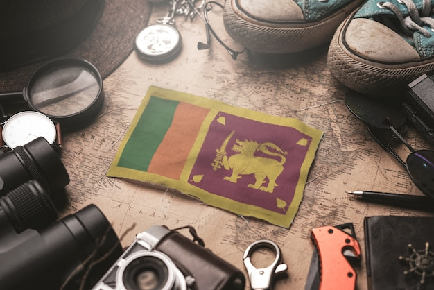 Sri lanka flag between traveler's accessories on old vintage map. tourist destination concept. Premium Photo