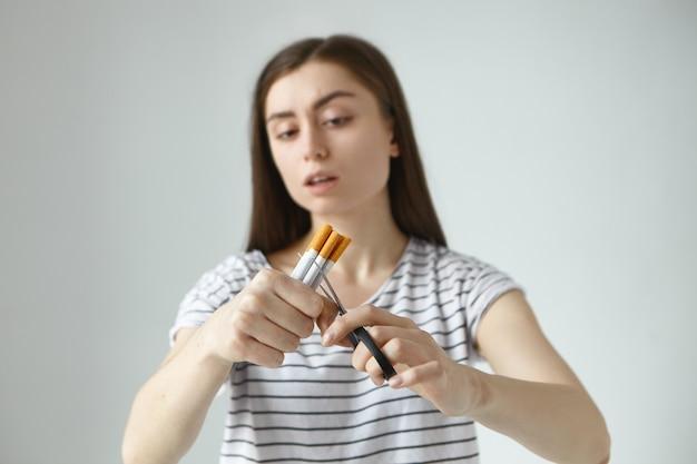 タバコとはさみの束を持った縞模様のtシャツを着た真面目な若い黒髪の女性は、喫煙をやめ、悪い習慣を永遠に断念することを決心したので、それらを半分に切りました。セレクティブフォーカス 無料写真