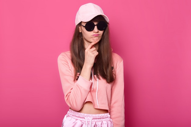Srusio shot of stylish teenager girl wearing fashionable shortened pink hoodie, cap and black subglasses, touches her chin with thoun ghtful facialexpression. female. people concept. Premium Photo