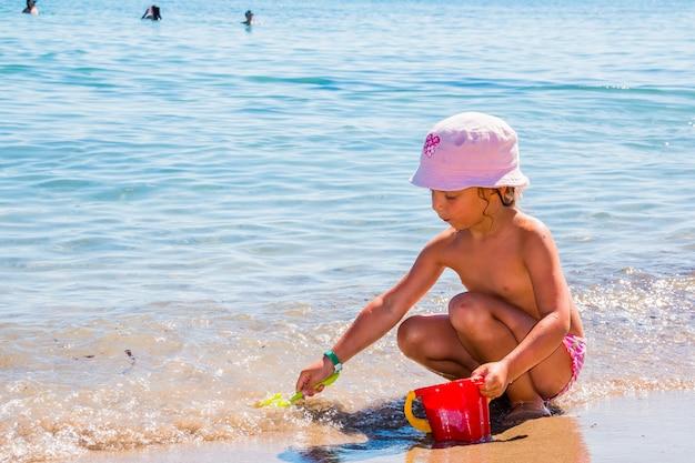 Маленькая девочка, играя на пляже с красным ведром и лопатой. маленький малыш малыш ssitting в воде наедине с шляпой солнца в солнечный летний день. дети играют с игрушками пляжа на тропическом пляже. Premium Фотографии