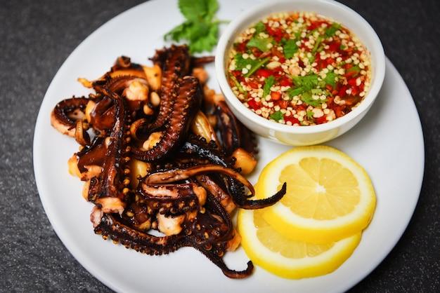 Салат из осьминога с лимонными травами и специями на белом фоне. ssquid жареная закуска еда острый и острый соус чили. Premium Фотографии