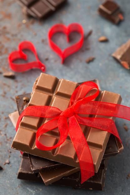 聖バレンタインデー。灰色のテーブルに赤いribbonndハートで結ばれたチョコレート Premium写真