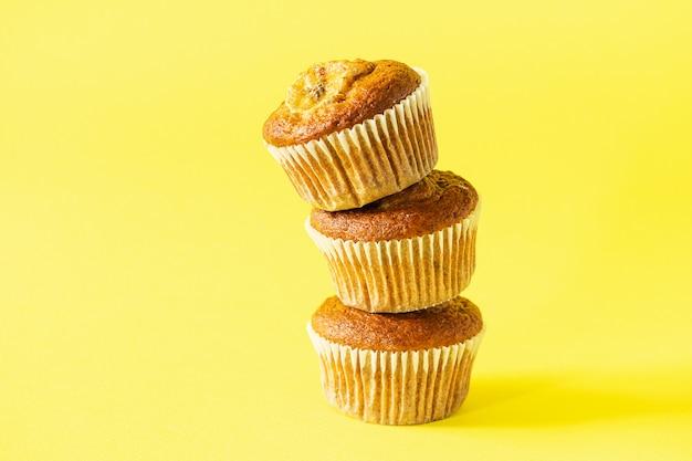 Stack of banana muffins on a yellow background. healthy vegan dessert. Premium Photo