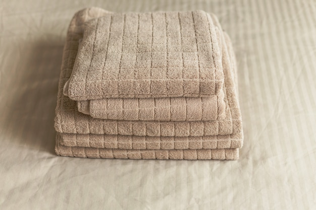 Stack of beige hotel towel on bed in bedroom interior. vintage toning Premium Photo