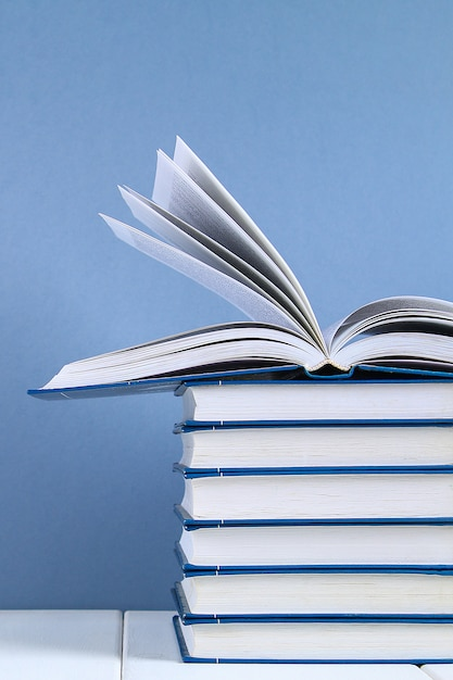 A stack of books on blue background. one hidden book on top of the pile. Premium Photo