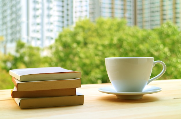 Stack of books and a cup of hot drinks on table by the window with green foliage and high building Premium Photo