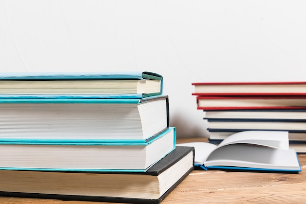 Stack of books on minimalistic wooden table Free Photo