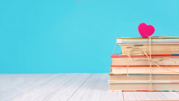 Stack of books and pink heart Premium Photo