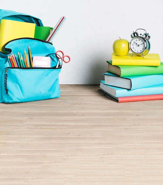 Stack of books and school backpack on floor Free Photo