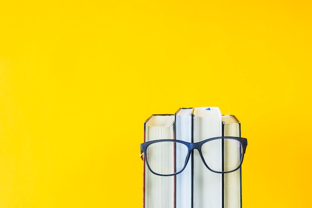 A stack of books with glasses is an image of a person's face Premium Photo
