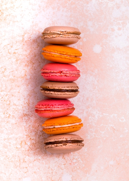 Stack of brown; orange and pink macaroons on textured weathered backdrop Free Photo