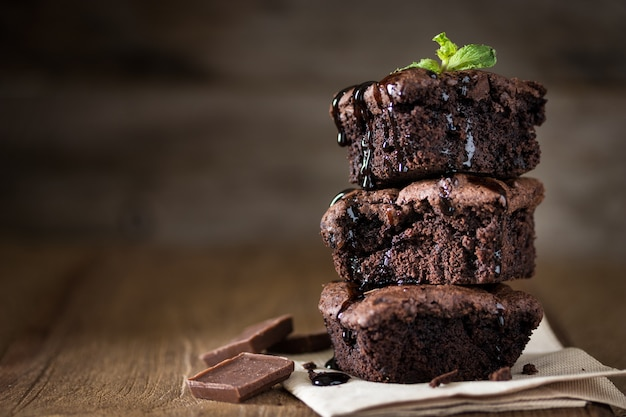 A stack of chocolate brownies on wooden background with mint leaf on top Premium Photo