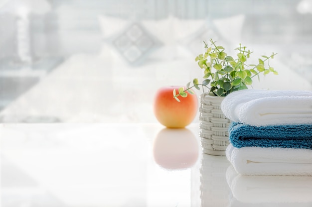 Stack of clean towels on white table with blur of bed room, copy space for product display. Premium Photo