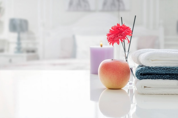 Stack of clean towels on white table with blur of bed room. Premium Photo