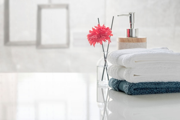 Stack of clean towels on white table with blur of living room, copy space for product display. Premium Photo
