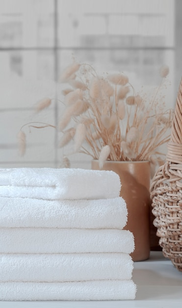 Stack of clean white towels on the table, vertical view. Premium Photo