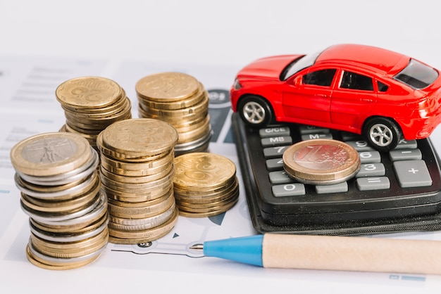Stack of coins; calculator; toy car and pen on template Free Photo