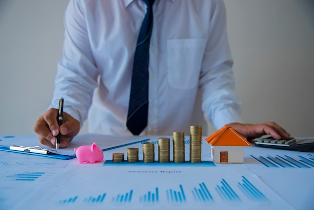 Stack of coins or coin pile on paper graph at office, business finance and money saving concept. Premium Photo