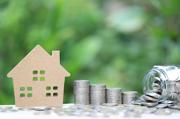 Stack of coins money and model house on natural green background Premium Photo