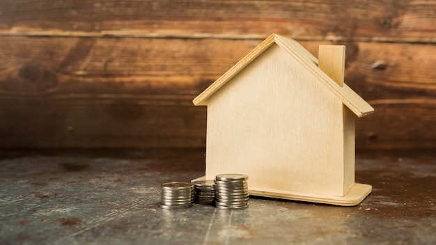 Stack of coins near the wooden house on floor Free Photo