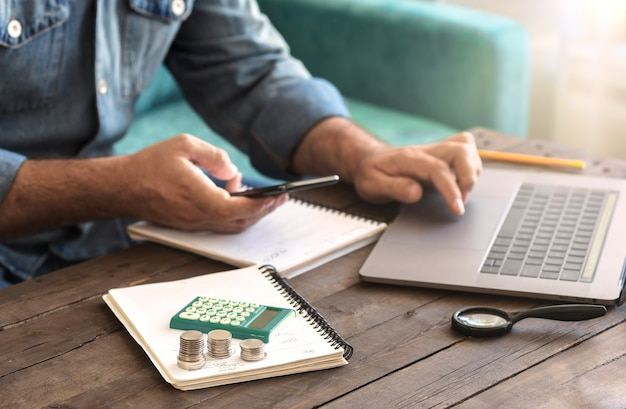 Stack of coins with a calculator on a wooden table. man examining home finance or starting new business concept Premium Photo