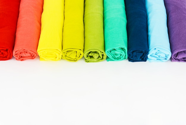 Stack of colorful t-shirt rolled up on white background Premium Photo