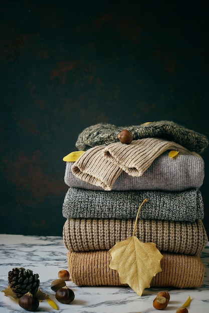 Stack of cozy knitted sweaters. autumn-winter concept, knitted wool sweaters. pile of knitted winter clothes, sweaters, knitwear Free Photo