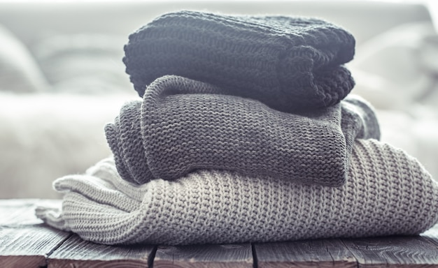 Stack of cozy knitted sweaters in different colors. Free Photo